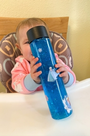 baby with snowstorm glitter sensory bottle