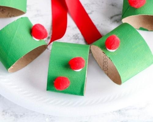 red pom poms glued to green cardboard pieces