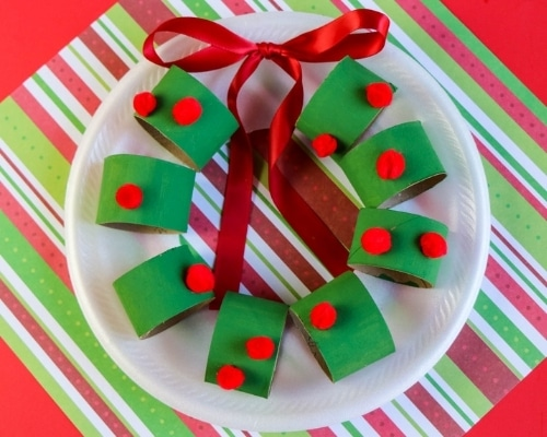 paper plate christmas wreath craft on colorful paper